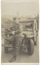 Kenneth Harrison Hill in front of a jeep
