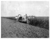 A group of men pose with a tractor in a field in Thomas County, Kansas
