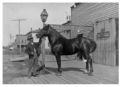 A man poses with a horse outside the Pratt Brothers livery stable, Colby, Thomas County, Kansas