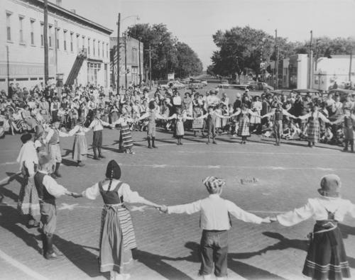 View of costumed children dancing on a street in Lindsborg, Kansas as part of its Svensk Hyllnings Fest activities, Oct. 1961