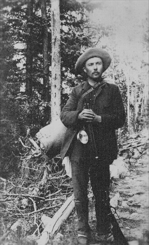 Informal portrait of Frederick Funston with a bedroll, metal cup, and rifle, 1890s