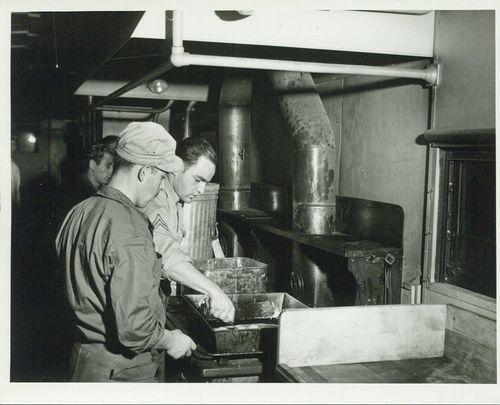 Cooks preparing a meal in a kitchen car on an Atchison, Topeka & Santa Fe Railway troop train - Page