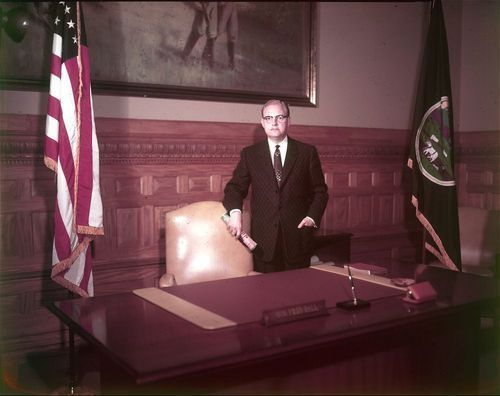Frederick (Fred) Lee Hall, Kansas governor, 1955-1957, standing by his desk. - Page