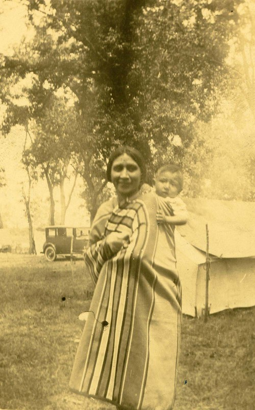 Photograph of Mrs. Kennedy, a Kansa Indian, carrying a baby at a Centennial Celebration in Council Grove, Kansas,  Aug. 14, 1925.
