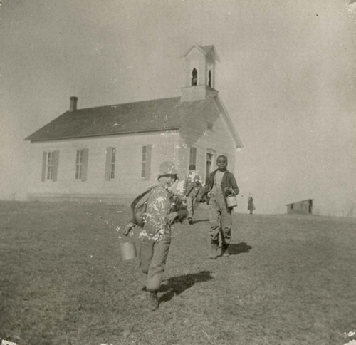 Photograph of three boys with lunch pails walking from the Blue Mound School near Valley Falls in Jefferson County, between 1900 and 1929