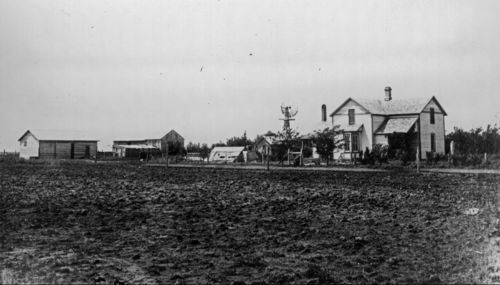 Photograph of the house, windmill, and farm buildings of the W.M. Criss farm in Scott County, Kansas.