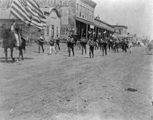 Image of a parade in Hill City, Kansas, including a marching band, spectators, horse-drawn carriages, and business buildings along the town street, 1890s.