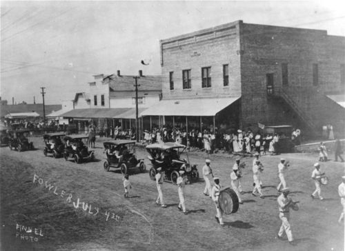 View of a marching band and automobiles in an Independence Day parade on July 4, 1908, in Fowler.