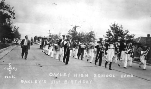 Photograph of the Oakley High School Band (known as the Oakley Oakes) performing in a parade in celebration of the 51st anniversary of the founding of Oakley, 1936