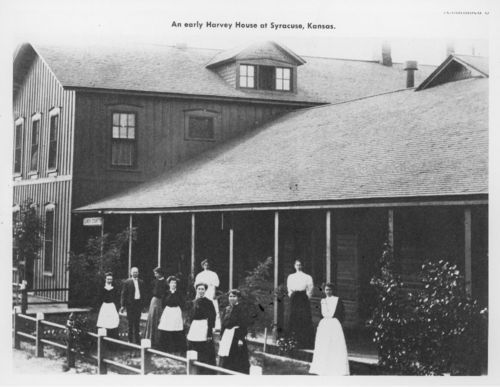 Photo of Harvey Girls standing outside of the Harvey House at Syracuse, Kansas, between 1885 and 1899.