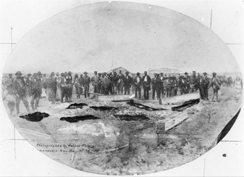 A photograph showing a large group of men looking at the  graves of those murdered by the Bender family, May 1873