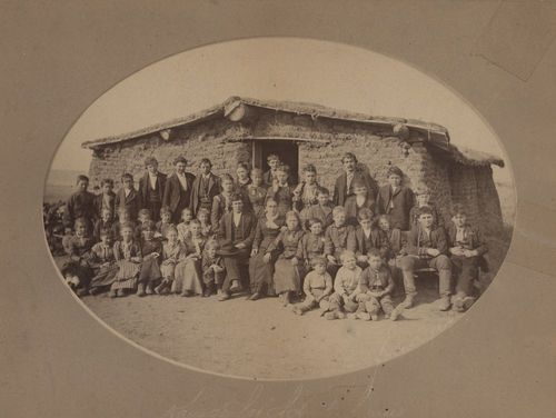 A sepia colored photo of a group of students in front of a sod schoolhouse.