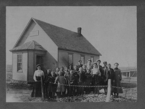 Photograph showing students and teacher Myrtle Matchett posed in front of Center Hill school, School District N 57, Hamilton County, between 1905 and 1909.