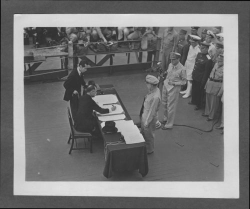 United States and Japanese officials signing the surrender document ending World War II - Page