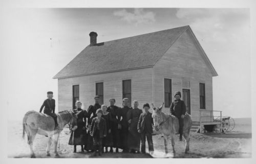 Photo depicting a group of students with their teacher in front of a one-room schoolhouse in Greeley County, Kansas, 1880s.