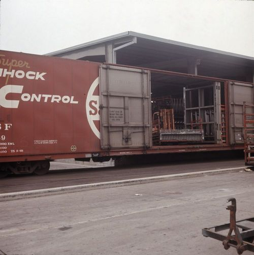 Unloading Ford auto parts from an Atchison, Topeka & Santa Fe Railway boxcar - Page