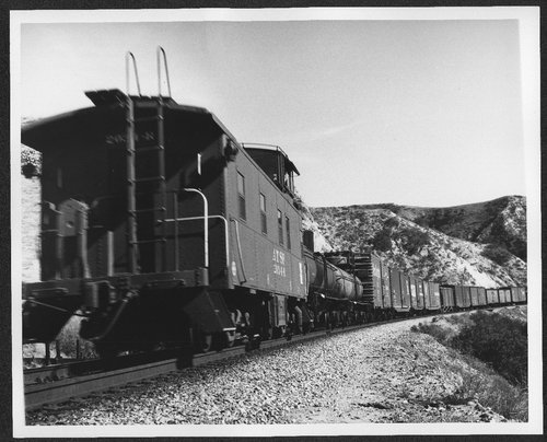 Atchison Topeka & Santa Fe caboose 2034-R at the end of a manifest train in Cajon Pass, California. - Page