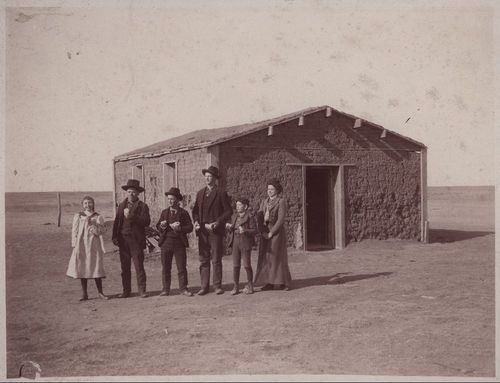 Sepia colored photo of a group of students and their teacher standing before a sod schoolhouse in district number thirty-eight, Thomas County, 1897.