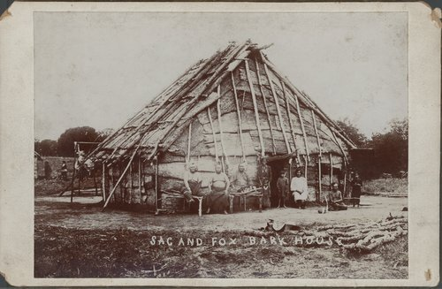 A photograph showing Sak and Fox tribe members, adults and children, posed by a bark house.