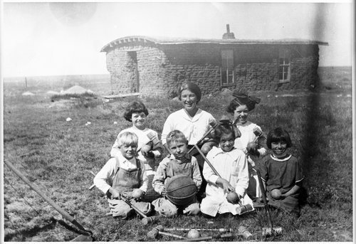 View of children with a ball and croquet equipment in front of a sodhouse, Greeley County, Kansas, between 1900 and 1905