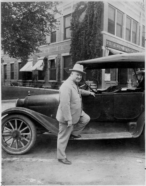 Photograph of William Allen White standing next to a Dodge automobile in front of the Emporia Gazette newspaper office during his campaign against the Ku Klux Klan, 1924