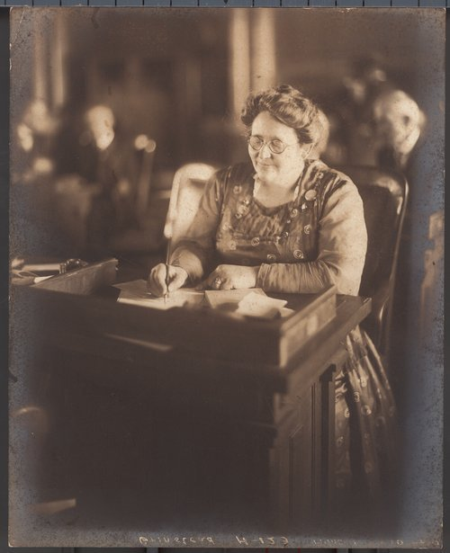 A photograph of Minnie Tamar Johnson Grinstead at her desk in  the Kansas House of Representatives, 1923