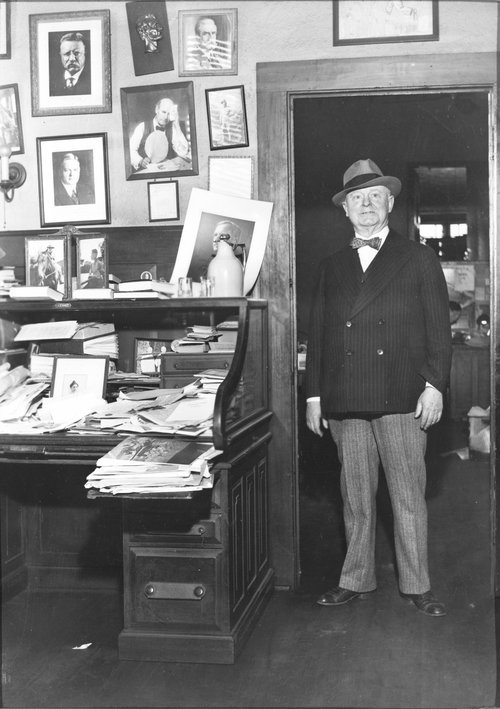Photograph showing William Allen White standing next to his  desk, 1930s