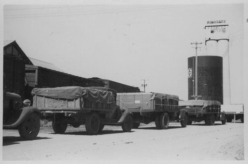 Grain trucks waiting at the elevator, Cimarron, Kansas - Page