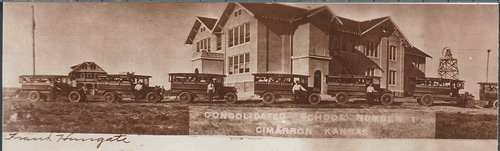 Photograph showing buses parked in front of Consolidated School Number 1, Cimarron, 1920s