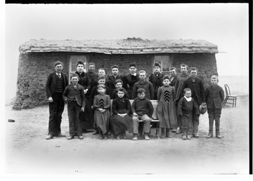 Photograph of students in front of a sod school house in Sheridan County, between 1885 and 1900.