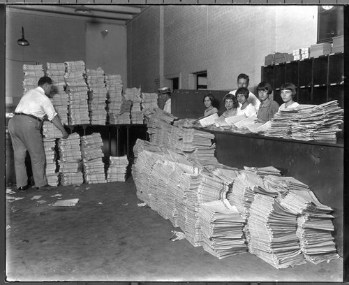 Photograph showing a group of girls sorting newspapers at a unidentified circulation office in Iola.