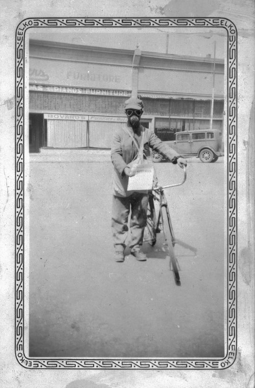Newspaper carrier wearing a dust mask, Ness City, Kansas - Page