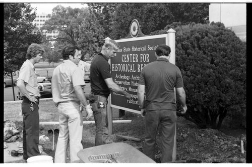 Employees of the Kansas State Historical Society installing a sign - Page