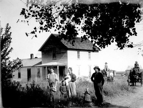 Unidentified family standing in front of their farmhouse in Finney County, Kansas - Page