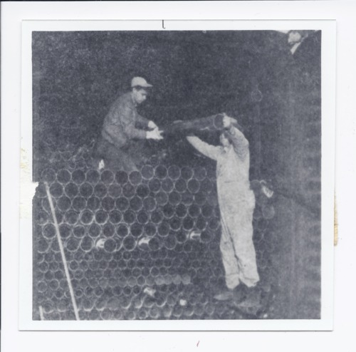 Leo Dale Berry and Carl Rupin unloading irrigation pipe, Rossville, Kansas - Page
