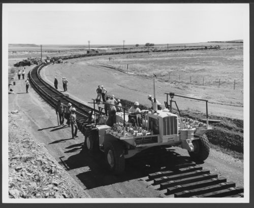 Atchison, Topeka & Santa Fe Railway's straddle buggy pulls welded rails near French, New Mexico - Page