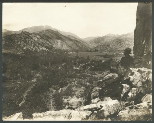 Man seated on rocks looking at the mountains probably in Colorado - Page
