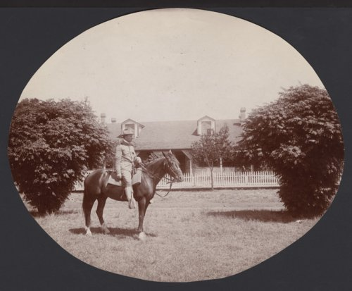 Soldier on a horse in front of an unidentified house possibly in Seward County, Kansas - Page