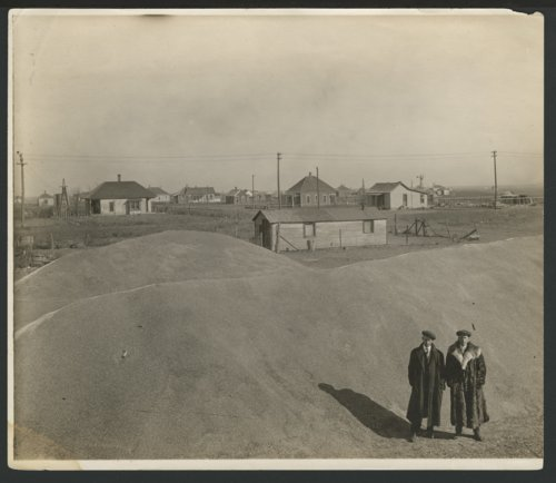 Two men standing by either piles of gravel or grain possibly in Liberal, Kansas - Page