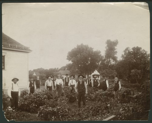 Men standing in a flower garden in Liberal, Kansas - Page