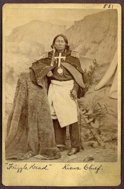 Kiowa chief, Frizzle Head pictured in the late 1870s. The photograph was taken after the Kiowa agreed to settle on the reservation. Frizzle Head?s clothing shows the transition from traditional bison skin clothing to cloth. He is also pictured wearing Euro-American style boots.