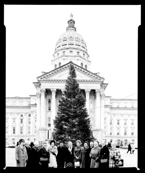 Governor Robert Docking standing by a Christmas tree on the capitol grounds - Page