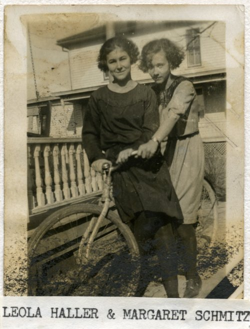 Leola Haller and Margaret Schmitz on a bicycle in Alma, Kansas - Page