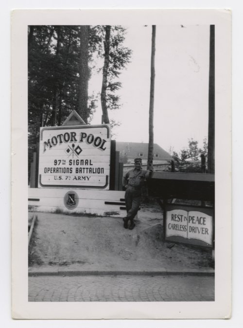 Paul H. Meadows standing by the U. S. 7th Army, 97th Signal Operations Battalion motor pool sign in Germany - Page