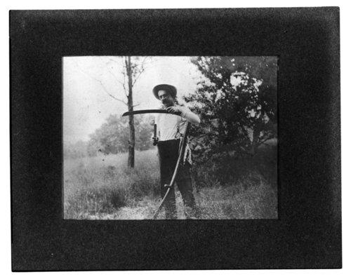 H. B. Jackson sharpening a scythe on his farm near Clements, Kansas - Page