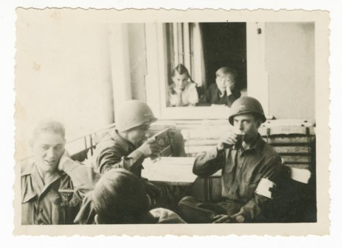 Soldiers drinking, German children in background - Page