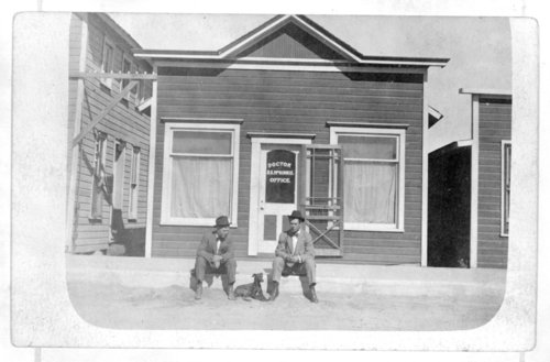 Roy Martin and Dr. S. S. McGinnis sit in front of Dr. McGinnis' office, Tribune, Greeley County, Kansas - Page