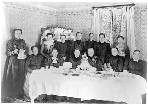A group of pioneer women sitting at a table filled with food, Greeley County, Kansas - Page