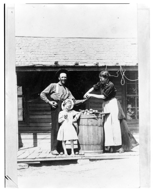 Family gathered around a potato barrel, Greeley County, Kansas - Page