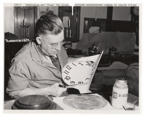 Atchison, Topeka & Santa Fe Railway employee cutting out a clock dial - Page